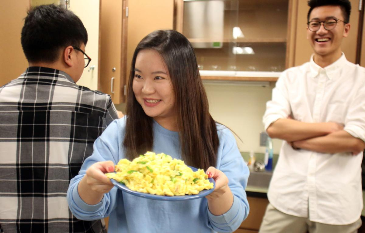 LCI student holding a plate of eggs and tomatoes