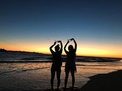 students in front of a sunset on a beach