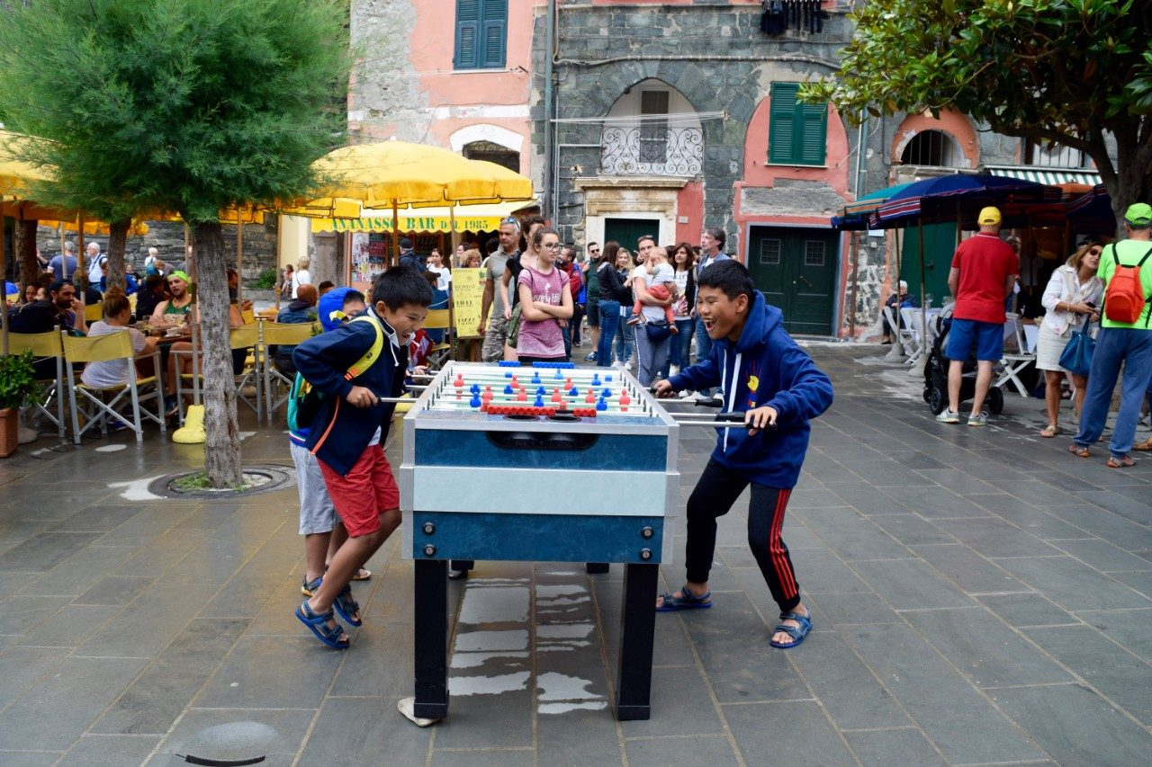 SYDNEY DELBRIDGE, MANAROLA, CINQUE TERRE, ITALY: Kids partake  in an intense game of foosball as tourists watch.