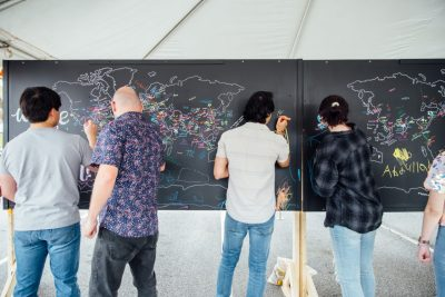 People writing on an outdoor chalkboard